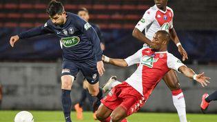 Le joueur de Rumilly Vallières Mathieu Guillaud échappe au défenseur de l'AS Monaco Djibril Sidibé durant la demi-finale de la Coupe de France à Annecy le 13 mai 2021. (PHILIPPE DESMAZES / AFP)