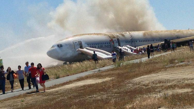 Des passagers évacuent le Boeing 777 d'Asiana Airlines, le 6 juillet 2013, après son atterrissage raté à l'aéroport de San Francisco (Etats-Unis). (EUGENE ANTHONY RAH / REUTERS)