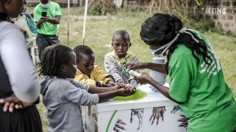 Une femme apprend à des enfants comment se laver correctement les mains devant un hôpital de Nairobi, au Kenya, le 18 mars 2020. (LUIS TATO / AFP)