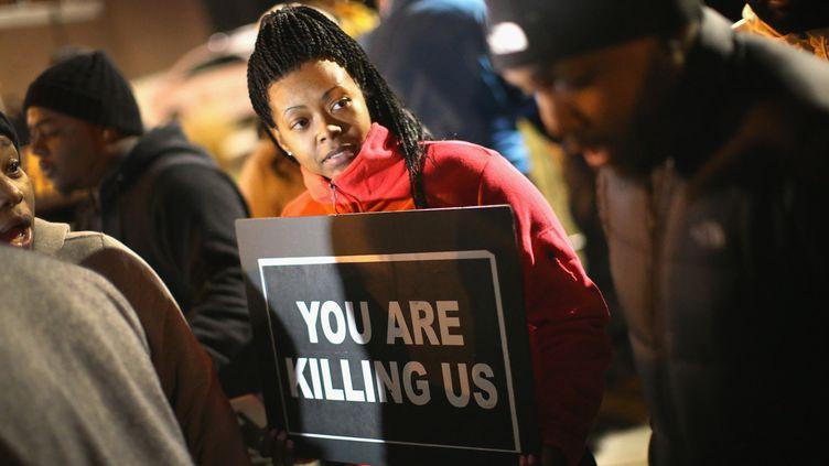 Une femme manifeste contre les violences policières, le 24 novembre 2014, devant le commissariat de Ferguson (Missouri). (SCOTT OLSON / GETTY IMAGES NORTH AMERICA / AFP )