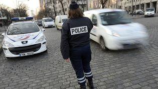 Une agent de police contrôle des véhicules, le 23 mars 2015, alors que la circulation alternée est mise en place dans Paris et 22 communes limitrophes. (LIONEL BONAVENTURE / AFP)