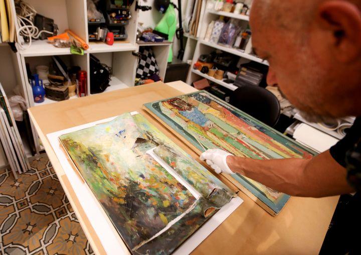 Gaby Maamary, restaurateur d'art libanais, examine une peinture de l'artiste Elie Kanaan, endommagée pendant l'explosion au port de Beyrouth. (ANWAR AMRO / AFP)