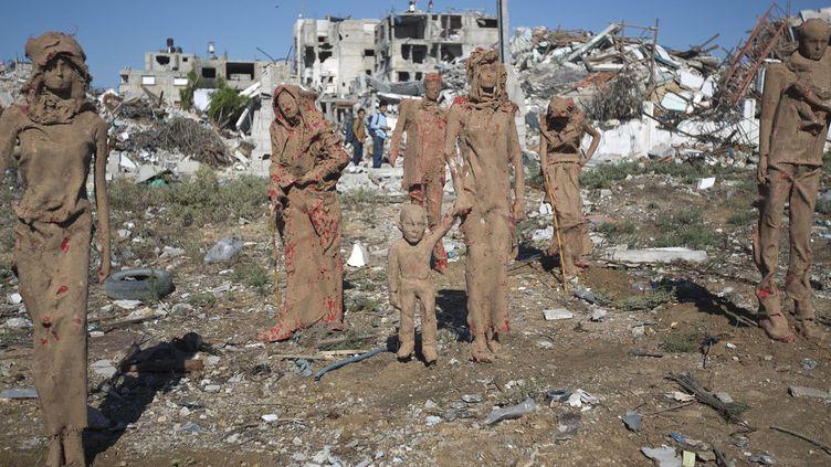 Certanes des statues en argile de Iyad Sabbah sont couvertes de tâches rouges.  (MAHMUD HAMS / AFP)