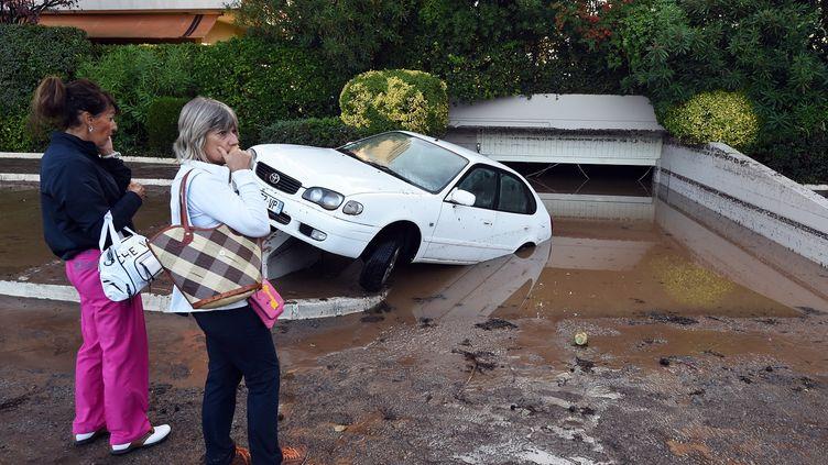 Des habitantes deMandelieu-la-Napoule (Alpes-Maritimes) passent devant un parking souterrain rempli de boue après les orages violents qui ont touché le département, le 4 octobre 2015. (BORIS HORVAT / AFP)