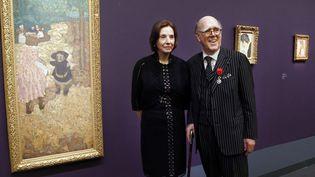 """Le couple Hays posent à côté de l'oeuvre d'Edouard Vuillard, """"Les Premiers Pas"""" (1894)à l'occasion de l'exposition de leur collection en 2013 au Musée d'Orsay.  (FRANCOIS GUILLOT / AFP)"""