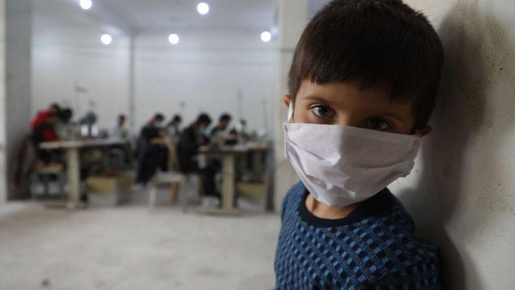 Un enfant syrien dans un atelier de couture où des volontaires fabriquent des masques pour lutter contre le coronavirus, à Idleb. (AAREF WATAD / AFP)