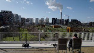 Une femme regarde unjardin communal de Saint-Ouen en Seine-Saint-Denis qui doit accueillir le futur village des athlètes pour les JO 2024. (LUDOVIC MARIN / AFP)
