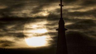 Eclipse solaire partielle aperçue entre les nuages au-dessus de la basilique du Sacré Coeur de l'université de Notre Dame (Indiana, Etats-Unis), le 23 octobre 2014. (ROBERT FRANKLIN / AP / SIPA)
