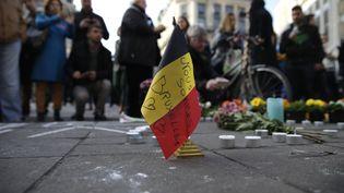 """Un drapeau belge marqué de """"Nous sommes tous Bruxelles"""" est déposé sur le mémorial improvisé, place de la Bourse à Bruxelles, après les attentats qui ont frappé la capitale belge mardi 22 mars 2016. (KENZO TRIBOUILLARD / AFP)"""