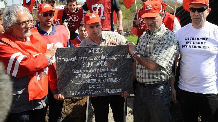 """Les employés de Florange et syndicalistes de FO, avec la plaque dénonçant la """"trahison"""" de François Hollande, le 24 avril 2013. (JEAN-CHRISTOPHE VERHAEGEN / AFP)"""