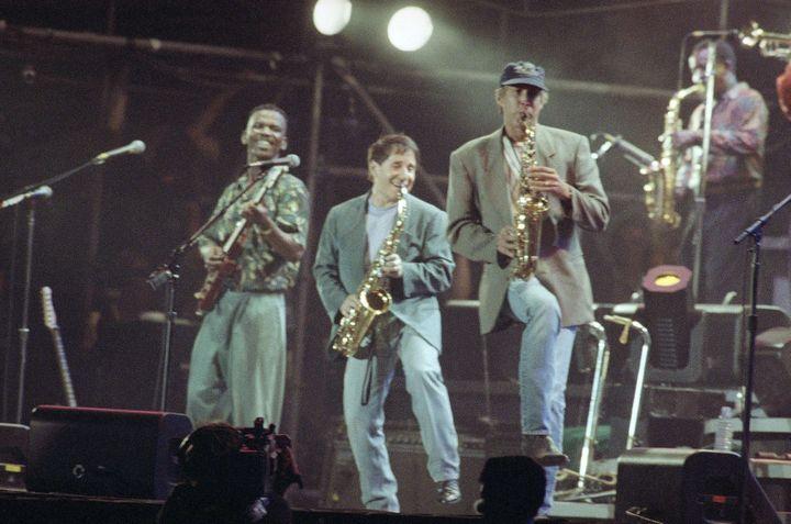 A gauche, à la guitare, Ray Phiri, avec Paul Simon (au centre) et Chevy Chase à droite, en concert à Central Park à New York, le 16 août 1991.