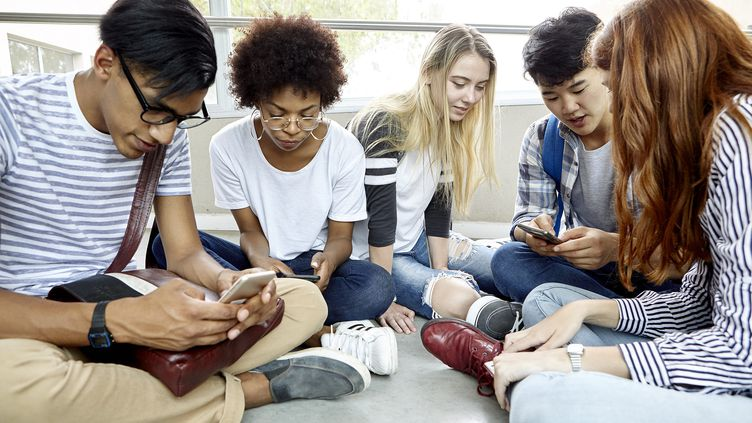 Des étudiants assis ensemble qui utilisent leur smartphone. (illustration) (DINOCO GRECO / MAXPPP)