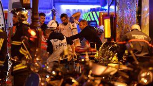 Des secouristes prenant en charge des blessés à Paris, peu après les attaques terroristes qui ont fait 130 morts et plus de 350 blessés, le 13 novembre 2015 dans la capitale. (MUSTAFA YALCIN / ANADOLU AGENCY / AFP)