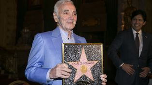 Charles Aznavour tient une étoile honorifique, le 27 octobre 2016 à Hollywood (Californie, Etats-Unis), semblable à celle qui sera cimentée sur le Walk of Fame. (JONATHAN ALCORN / AFP)