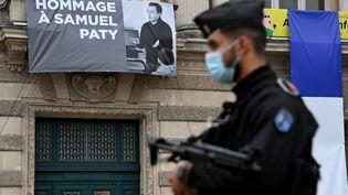 Un policier devant une banderole d'hommage à Samuel Paty, à Montpellier, le 21 octobre 2020 (PASCAL GUYOT / AFP)