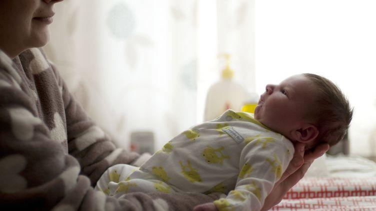 Un bébé dans les bras de sa mère (NEVILLE MOUNTFORD-HOARE / MAXPPP)