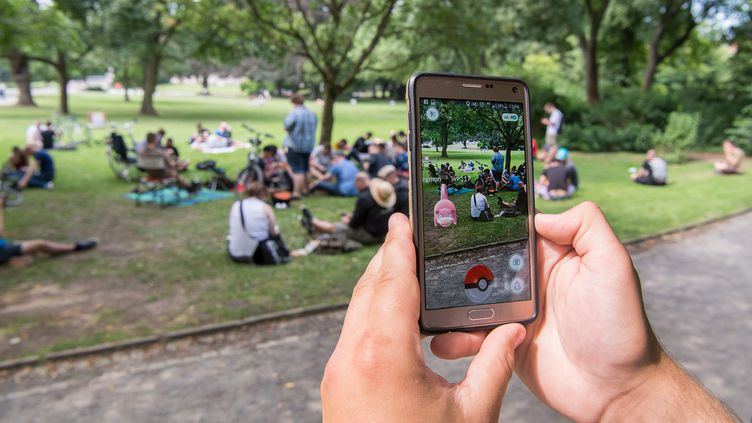 Un utilisateur de Pokémon Go tente de capturer un Ramoloss dans un parc à Hanovre, en Allemagne, le 13 juillet 2016, jour de la sortie de l'applicationdans le pays. (SEBASTIAN GOLLNOW / AFP)