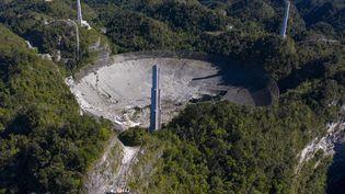 Cette vue aérienne montre les dégâts à l'observatoire d'Arecibo après la rupture d'un des principaux câbles retenant le télescope, à Porto Rico, le 1er décembre 2020. (RICARDO ARDUENGO / AFP)
