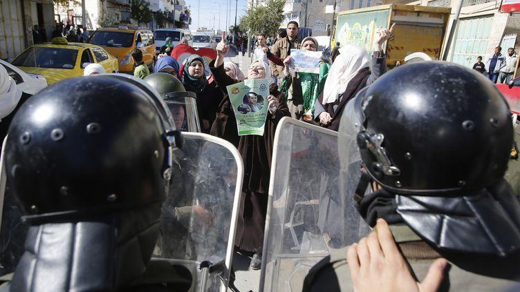 Des membres des forces de sécuritépalestiniennes font face à des manifestants qui protestent contre Israël, le 7 novembre 2014, à Hébron, enCisjordanie. (MUSSA QAWASMA / REUTERS)