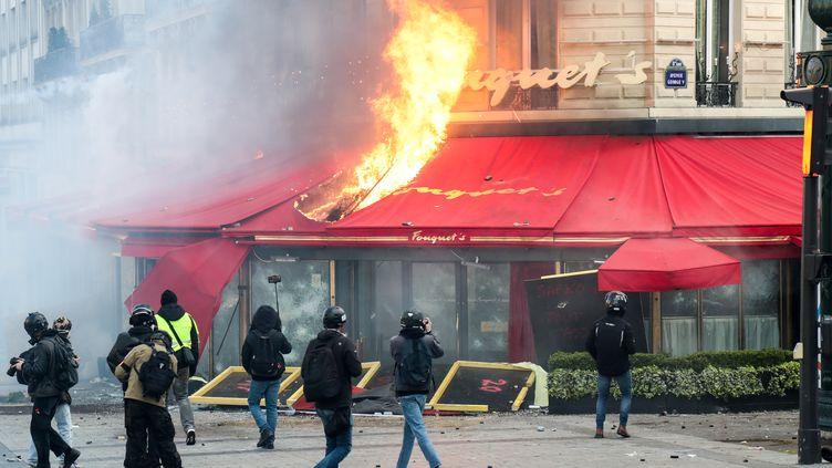 Le restaurant Fouquet's en flammes, le 16 mars 2019 à Paris. (ZAKARIA ABDELKAFI / AFP)