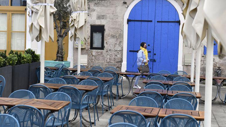 Une passante devant la terrasse d'un restaurant fermé à Marseille (Bouches-du-Rhône), lundi 28 septembre 2020. (NICOLAS TUCAT / AFP)