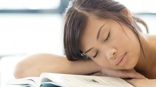 Jeune femme endormie sur un livre. Photo d'illustration. (ERIC AUDRAS / MAXPPP)