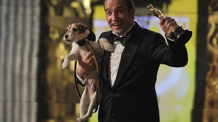 Jean Dujardin pose avec son Oscar, le chie Uggie dans les bras, le 26 février 2012 à Los Angeles (Etats-Unis). (ROBYN BECK / AFP)