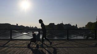 Une femme tente de combiner promenade en poussette et activité sportive sur le Pont des Arts à Paris, en avril 2020. (ALAIN JOCARD / AFP)
