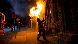 Un pompier intervient sur un incendie à Baltimore (Etats-Unis), le 28 avril 2015, alors que la ville est secouée par des émeutes. (ERIC THAYER / REUTERS)