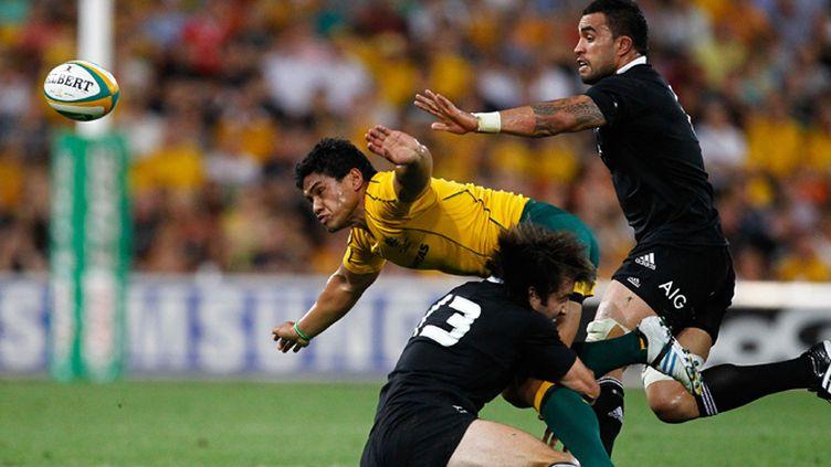 Ben Tapuai (Australie) plaqué par le All Black Conrad Smith sous le regard de Liam Messam (Nouvelle-Zélande)