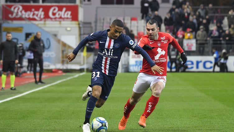 Le joueur du PSG Colin Dagba au duel avec Yohan Court; le joueur du Stade Brestois (DAMIEN MEYER / AFP)