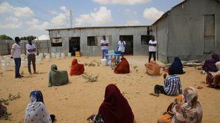 Des volontaires distribuent des produits d'hygiène dans un camp de réfugiés à Mogadiscio, en Somalie, pour lutter contre la propagation du coronavirus le 2 avril 2020. (SADAK MOHAMED / ANADOLU AGENCY)