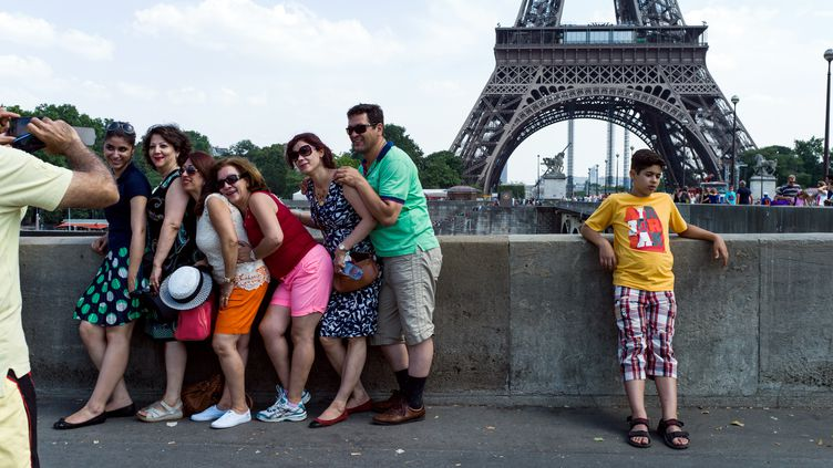 Des touristes devant la tour Eiffel, à Paris, le 9 juillet 2013. (FRED DUFOUR / AFP)