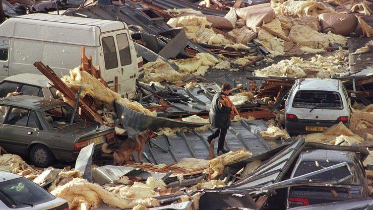 Une personne traverse les décombres de la toiture d'un immeublede Saint-Pierre-sur-Dives (Calvados), emportée par la tempête, le 26 décembre 1999 (MYCHELE DANIAU / AFP)
