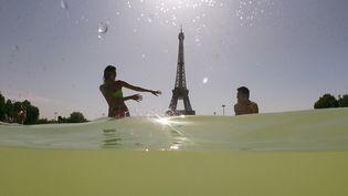 Des personnes dans la fontaine du Trocadéro, près de la tour Eiffel à Paris, le 25 juillet 2019. (DOMINIQUE FAGET / AFP)