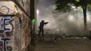 Un officier fédéral tire des gaz lacrymogènes sur une foule de manifestants à Portland, aux Etats-Unis, le 22 juillet 2020. (ZACH WILKINSON / SPUTNIK / AFP)