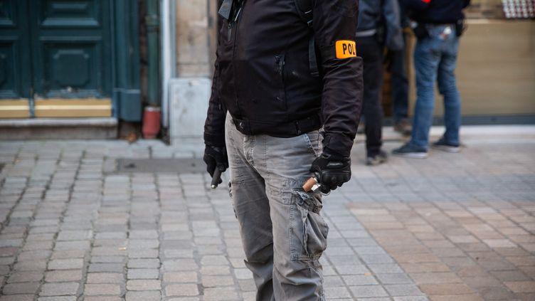 """Un policier de la BAC tient une grenade GLI-F4, lors de la manifestation pour marquer l'anniversaire du mouvement des """"gilets jaunes"""", à Nantes (Loire-Atlantique), le 16 novembre 2019. (JEREMIE LUSSEAU / HANS LUCAS / AFP)"""