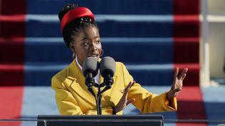 """Amanda Gorman, 22 ans, la jeune poétesselit """"The Hill We Climb"""", un texte de sa composition, lors de l'investiture du président américain Joe Biden le 20 janvier 2021. (POOL / GETTY IMAGES NORTH AMERICA)"""