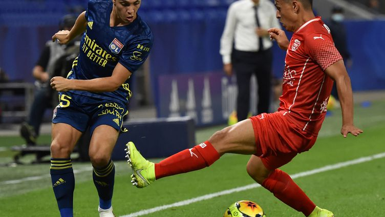 Le Lyonnais Maxence Caqueret face au Nîmois Andrés Cubas  (JEAN-PHILIPPE KSIAZEK / AFP)