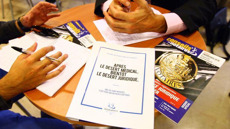 Discussion entre un notaire et son client au-dessus d'une brochure contre le projet du loi du gouvernement sur les professions règlementées, le 14 octobre 2014 à Perpignan (Pyrénées-Orientales). (  MAXPPP)