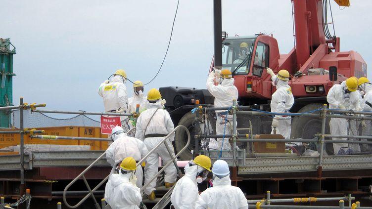 Des ouvriers deTokyo Electric Power Co (TEPCO) retirent des combustibles nucléaires de la centrale de Fukushima (Japon), le 18 juillet 2012. (TEPCO / AFP)