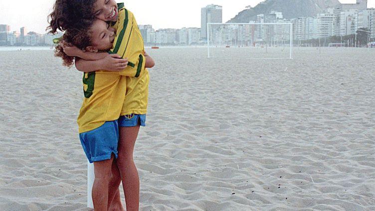 Deux amies brésiliennes s'étreignent sur la plage. (VANDERLEI ALMEIDA / AFP)