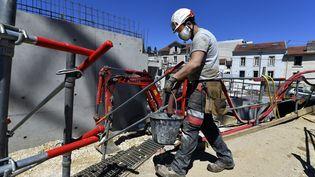 Un ouvrier porte un sceau sur un chantier. (Photo d'illustration) (ALEXANDRE MARCHI / MAXPPP)