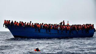 Des migrants attendent leur sauvetage au large de la Libye, en mer Méditerranée, le 3 octobre 2016. (ARIS MESSINIS / AFP)