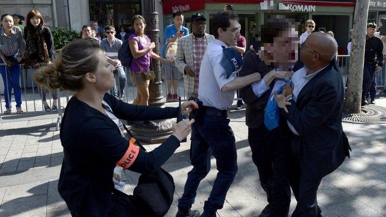 Interpellation d'un opposant au mariage homosexuel sur les Champs-Elysées le 14 juillet 2013. (MIGUEL MEDINA / AFP)