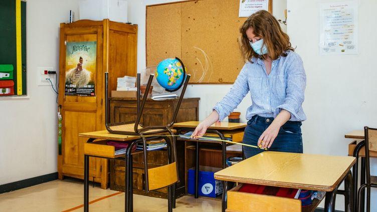 Une professeure des écoles mesure la distance entre deux tables, à l'école privée catholique Saint Jean Gabriel, à Paris, le 11 mai 2020. (MATHIEU MENARD / HANS LUCAS / AFP)