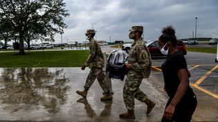 Des membres de la garde nationale assistent une femme lors de son évacuation à Lake Charles (Louisiane), le 8 octobre 2020. (CHANDAN KHANNA / AFP)