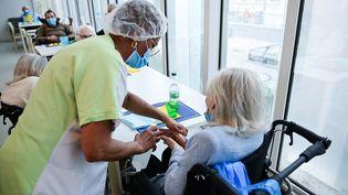 Une infirmière auprès d'une résidente de l'Ehpad Alice Prin, à Paris, le 4 mars 2021. (MARTIN BUREAU / AFP)