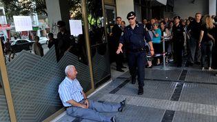 Un retraité pleure assis sur le sol devant une banque, à Thessalonique, en Grèce. (SAKIS MITROLIDIS / AFP)