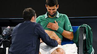 Novak Djokovic touché aux abdominaux lors du 3e tour de l'Open d'Australie 2021 contre Taylor Fritz, le12 février à Melbourne (DEAN LEWINS / AAP)